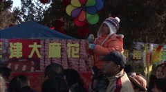 Chinese boy with a wind mobile & his father Stock Footage