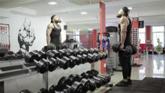 Man takes dumbbells and workout in the gym - stock footage