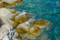 Coast with rocks on the beautiful turquoise Aegean Sea. Chalkidiki, Greece. Stock Photos