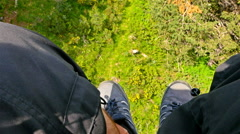 View from a ski lift to the green mountain, passenger's feet in the foreground Stock Footage