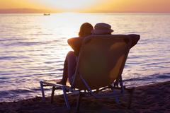 Woman and little girl sitting on sunbeds and relaxing on the beach at sunset. - stock photo