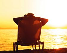 Silhouette of woman with hat , sitting on sunbeds at beach, enjoying sunset.  - stock photo
