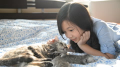 Beautiful asian girl lying with american shorthair cat - stock footage