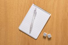 Empty notepad and dice Stock Photos