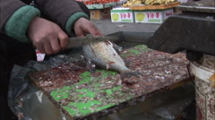 Chinese market, fishmonger gutting fish Stock Footage