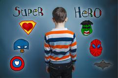 Adolescent boy turned and looks ahead rear view photo superhero Stock Photos