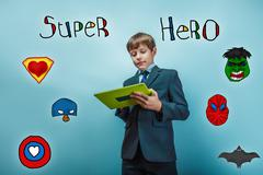 Boy in a suit style office holding a tablet superhero super powe Stock Photos