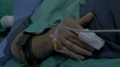 Stock Video Footage of Patient hand close up,tilt up,surgeon team operating eye cataract in background.