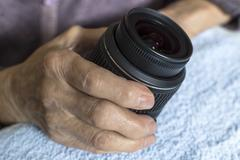 DSLR lens in old woman's hands. - stock photo