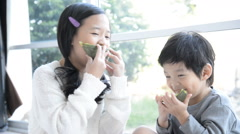 Asian children eating melon Stock Footage