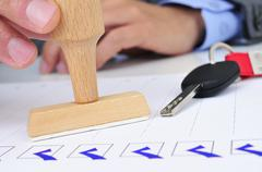 man in office with a rubber stamp and a car key - stock photo