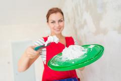 Woman plastering wall - stock photo
