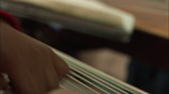 Hands strumming zither strings, music, China - stock footage