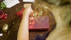 Over the Shoulder Shot of a Woman Wrapping a Gold Ribbon Around a Present Stock Footage