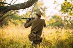 Unidentified re-enactor dressed as Soviet russian soldier aiming Stock Photos