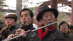 Chinese men playing flutes & trumpets Stock Footage
