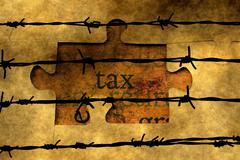 Tax puzzle concept against barbwire Stock Photos