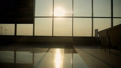 Silhouettes of passengers in the airport lounge at sunset Stock Footage