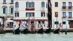 Gondolas moored at the pier in a Venetian canal, venice Stock Footage