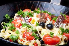 fresh pasta with tomatos and olives in a pan - stock photo
