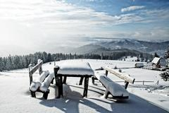 Table and bench covered by fresh snow after blizzard Stock Photos
