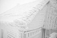 Snow covered house after blizzard - stock photo