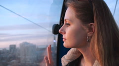 Travel: beautiful young woman tourist looking through the glass in the ropeway - stock footage