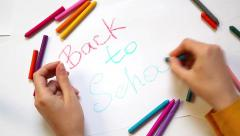 Hands writing back to school with colors on white background Stock Footage