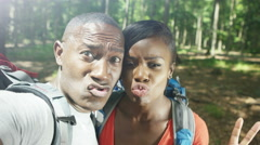 4K Portrait of attractive couple hiking in the woods, pulling faces to camera Stock Footage
