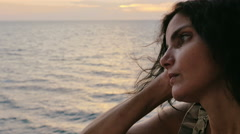 Sad girl looks at the sea wistfully at sunset Stock Footage