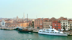 DOHC ancient vessel moored to a pier in front of some Venetian palaces Stock Footage