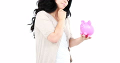 Thoughtful Asian woman holding and looking a piggy bank Stock Footage