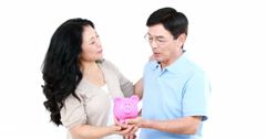 Mature Asian couple holding a piggy bank Stock Footage