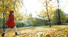 Happy girl 7 years old throws up leaves in the park in the autumn and laughin Stock Footage