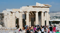 Tourists walking in front of ancient greek temple Stock Footage