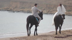Happy bride and groom riding on horses at the seashore - stock footage