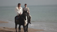 Beautiful bride and groom riding on horses at the seashore - stock footage