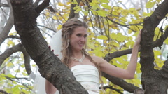 The bride looks at the fiance through the branches of the tree - stock footage