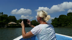 European woman takes photos with Samsung S6 in front of boat Stock Footage