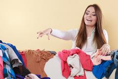 Happy woman picking clothes up in messy room. - stock photo