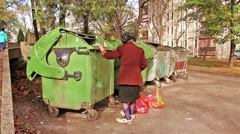 Homeless woman is searching for food in garbage dumpster - stock footage