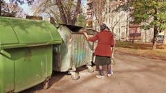 Woman in poverty is searching something in garbage dumpster - stock footage