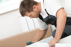 Man putting together self assembly furniture - stock photo