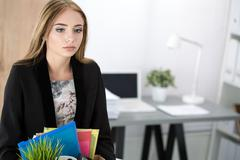 Young dismissed female worker in office holding carton box with her belonging Stock Photos