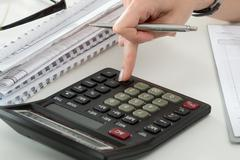 Close up of female accountant or banker making calculations - stock photo