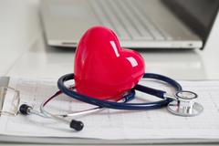 Read heart and stetoscope laying on cardiogram chart at doctor's working tabl Stock Photos