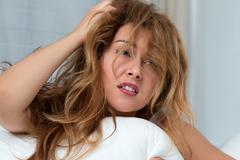 Young tousled woman waking up early - stock photo