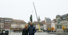 Couple walking towards camera while crane installs traditional Christmas Tree Stock Footage