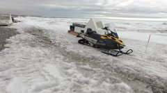 Arctic Landscape Snowmobile On Beach Ice And Snow Covered Water Walking Up Beach Stock Footage