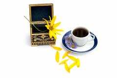 The open casket and cup of coffee decorated with florets Stock Photos